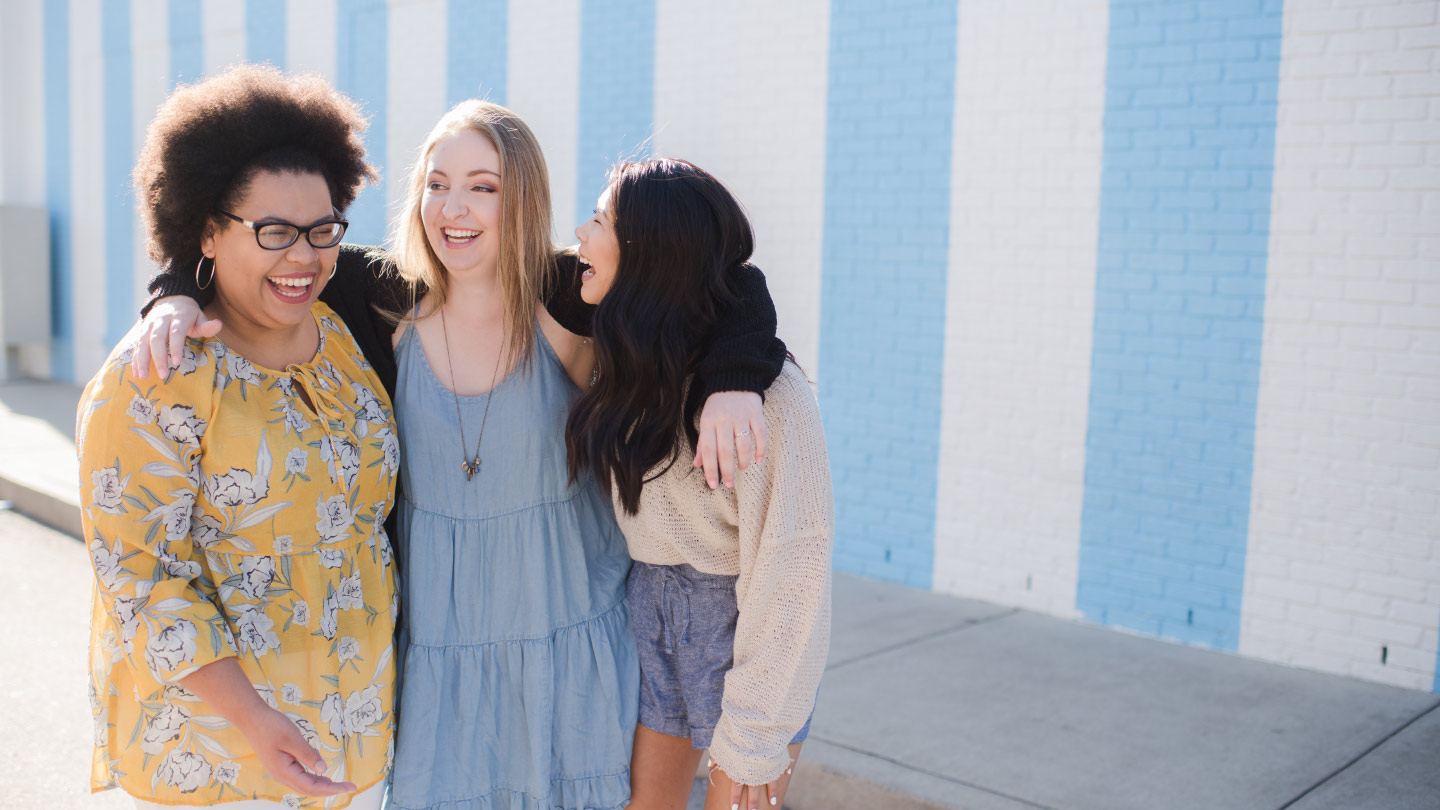Three college students hugging in front of a blue and white striped wall